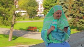 A young cheerful Muslim woman in a light scarf in the park is drinking coffee and talking in the messenger in headphones. The average plan stock video footage