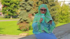 A young cheerful Muslim woman in a light scarf and sunglasses in the park drinks coffee and talks in the messenger with. Headphones. The average plan stock footage