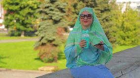 A young cheerful Muslim woman in a light scarf and sunglasses in the park drinks coffee and talks in the messenger with. Headphones. The average plan stock video