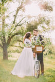 Young cheerful newlywed couple posing in park with bicycle Royalty Free Stock Photography