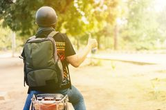 Young cheerful and positive male motorcyclist riding on motorbike on the country street. Stock Image