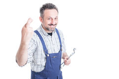 Young cheerful repairman with wrench making a wish Royalty Free Stock Photography