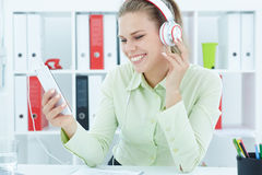 Young cheerful secretary  listening music in headphones at office. Royalty Free Stock Photography
