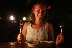 Young cheerful smiling woman holding spoon and fork in an outdoor cafe at the sea on beautiful bokeh lights Stock Photography