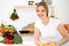Young cheerful smiling woman is ready for cooking in a kitchen. Housewife sitting at the table and looking at the camera.  Stock Photo