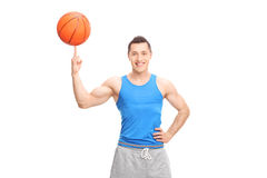 Young cheerful sportsman spinning a basketball. On his finger and looking at the camera isolated on white background Stock Photography