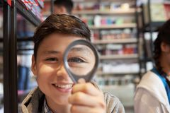 Boy with magnifier in library smiling. Young cheerful student boy standing in school library and looking at camera through loupe stock images