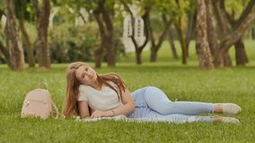A young cheerful student girl lies on the grass in an open-air park positively posing in the camera. Rest during study. A young cheerful student girl lies on Royalty Free Stock Photos