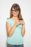 Young cheerful student using mobile phone Royalty Free Stock Image