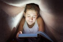 Young cheerful teenage girl hiding under blanket and reading boo. K in the darkness. Key light coming from book. Indoors horizontal image Royalty Free Stock Photography