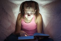 Young cheerful teenage girl hiding under blanket and reading book royalty free stock image
