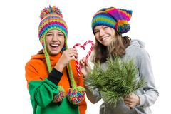 Young cheerful teenage girls having fun with Christmas candy canes, in winter knitted caps, isolated on white background.  royalty free stock photo