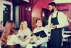 Young cheerful waiter taking care of adults Stock Photo