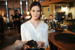 Young cheerful waitress hold paying terminal in hands and look straight on camera. Hand hold credit card upon terminal stock images
