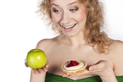 Young cheerful woman, between apple and cake Stock Images