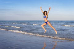 Young cheerful woman in bikini jumping on the beach. Royalty Free Stock Photography