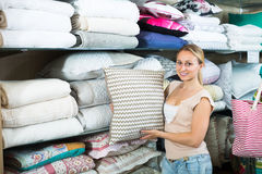 Young cheerful woman buying fluffy pillow Stock Images