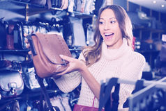 Young cheerful woman buying leather purse in shop Stock Photos