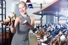 Young cheerful woman choosing from two pairs of shoes Royalty Free Stock Photos