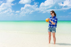 Young cheerful woman with coconut against turquoise sea Royalty Free Stock Photography