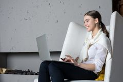 Young cheerful woman content manager or professional writer keyboarding on portable laptop computer, sitting in modern interior ne Stock Images