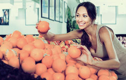Young cheerful woman customer choosing ripe oranges Stock Photo