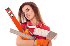 Young cheerful woman with dark hair in uniforl makes renovations with tools in her hands isolated on white background Royalty Free Stock Image