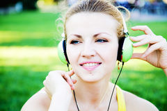 Young cheerful woman enjoing the music outdoors Royalty Free Stock Images