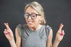 Young cheerful woman with fingers crossed Stock Photo