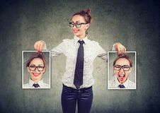 Cheerful woman showing different photos with emotions. Young cheerful woman in glasses holding pictures with good and bad emotions having mood swings and smiling royalty free stock photo