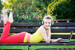 Young cheerful woman having rest in the park with laptop Royalty Free Stock Photography