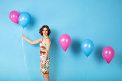 Young cheerful woman with helium balloons on a blue background. Royalty Free Stock Photography