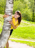 Young cheerful woman hold on birch Stock Image
