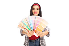 Young cheerful woman holding color swatch. And looking at the camera isolated on white background stock image