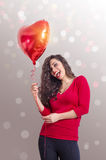 Young cheerful woman holding heart shaped balloon Royalty Free Stock Photography