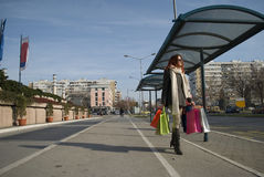 Young cheerful woman holding shopping bags at buss station. Young cheerful woman holding shopping bags at the buss station Royalty Free Stock Images
