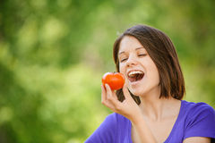 Young cheerful woman holding tomato Royalty Free Stock Photo