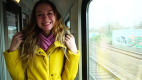 Young cheerful woman laughs and fools, showing gestures with hands in moving train near  window in  afternoon. stock video