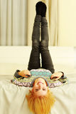 Young cheerful woman lying on the bed Stock Photos