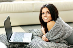 Young cheerful woman lying with laptop and looking away Stock Images