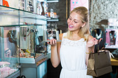 Young cheerful woman picking fashion earrings Royalty Free Stock Image