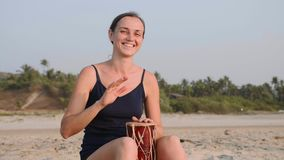 Young cheerful woman playing drums on sandy beach in slow motion. Happy woman having fun with ethnic drums outdoor stock video footage