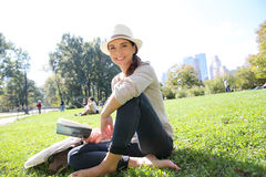 Young cheerful woman reading book sitting in central park Stock Photos