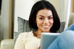 Young cheerful woman resting with tablet computer Stock Images