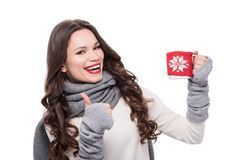 Young cheerful woman in scarf and arm warmers holding coffee mug and showing thumb up,. Isolated on white royalty free stock photos