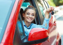 Young cheerful woman sitting in a car with keys in hand Stock Images