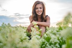 Young cheerful woman sitting outdoors in a field. royalty free stock images