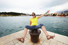 Young cheerful woman sitting on pier Stock Photo