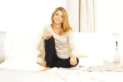 Young cheerful woman sittting on the sofa Stock Image
