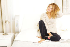 Young cheerful woman sittting on the sofa Royalty Free Stock Photography